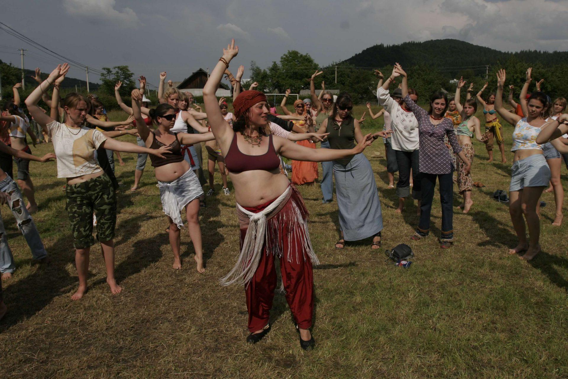 Дівчина показує танцювальні рухи, учасники майстер-класу повторюють все за нею на фестивалі в Шешорах