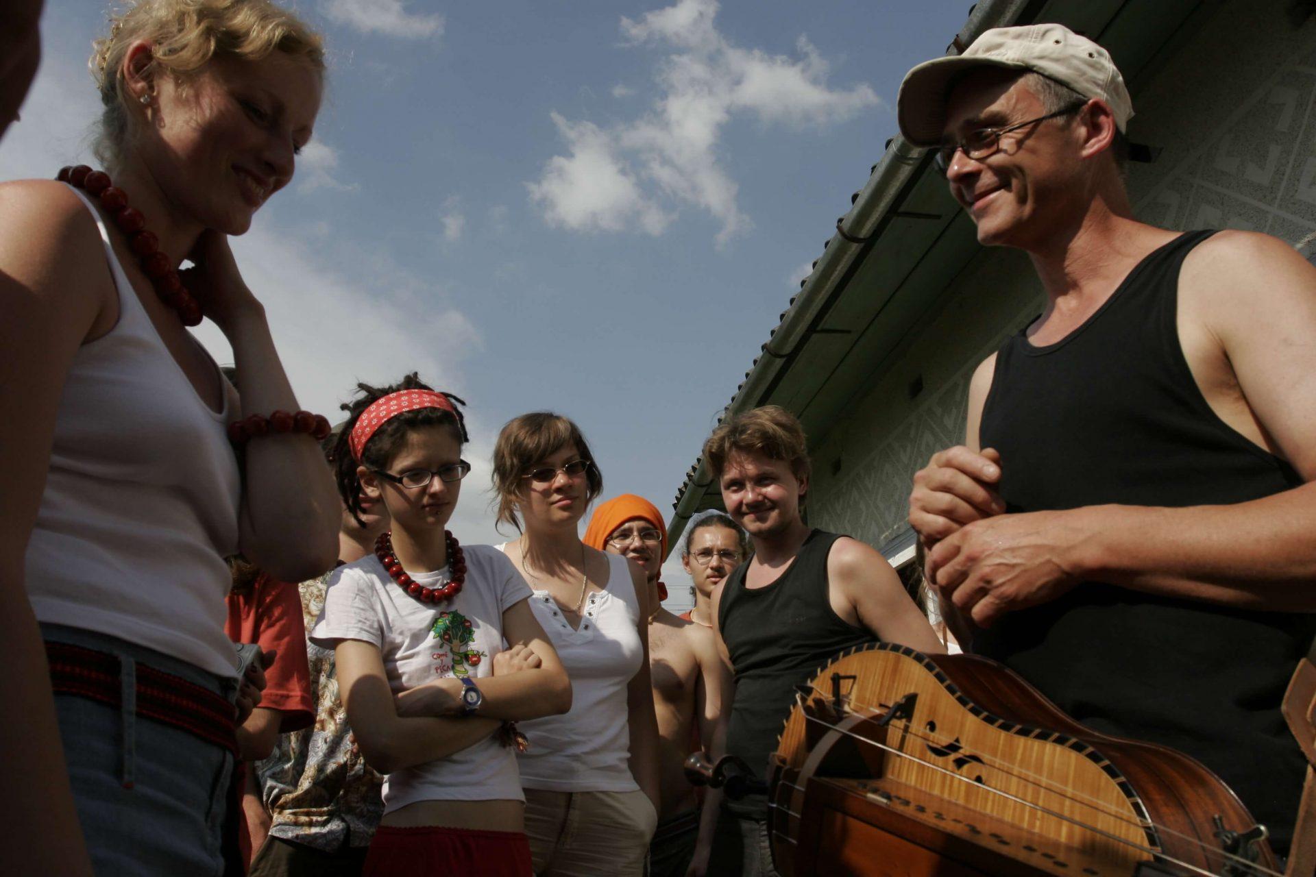 Учасники фестивалю дивляться на чоловіка, який тримає колісну ліру на фестивалі в Шешорах