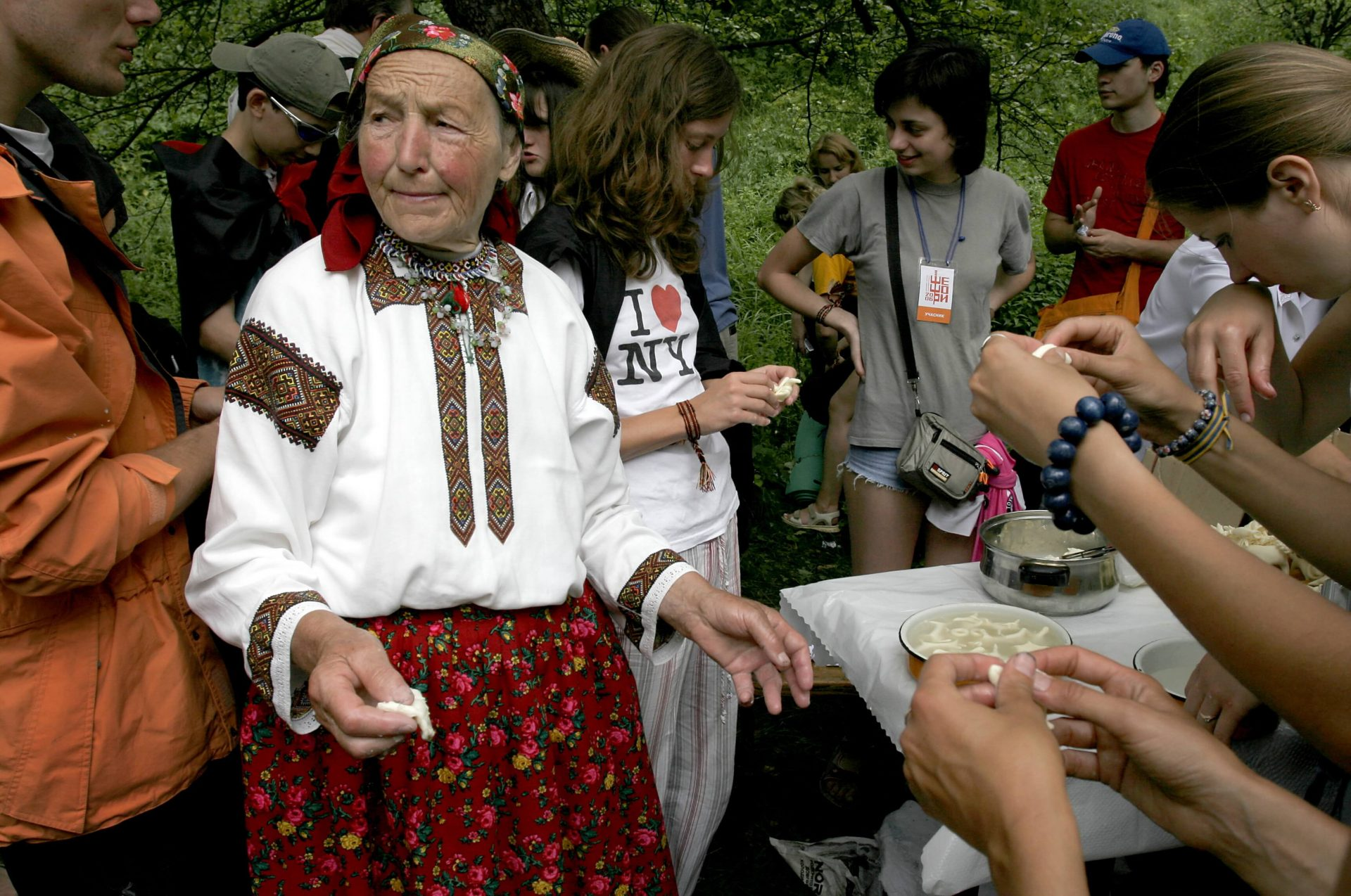 Майстриня в народному строї проводить майстер-клас із ліпки фігурок з тіста, навколо неї учасники фестивалю в Шешорах