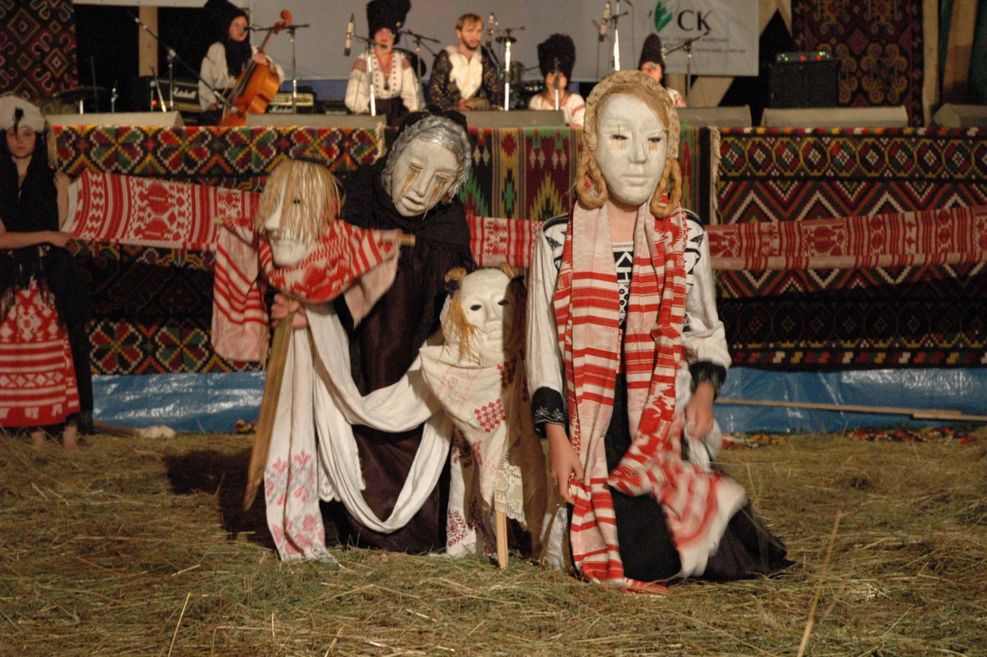 Під сценою двоє дівчат одягнуті в маски, тримають ляльок в таких самих масках та позують на камеру під виступ гурту «ДахаБраха» на фестивалі в Шешорах