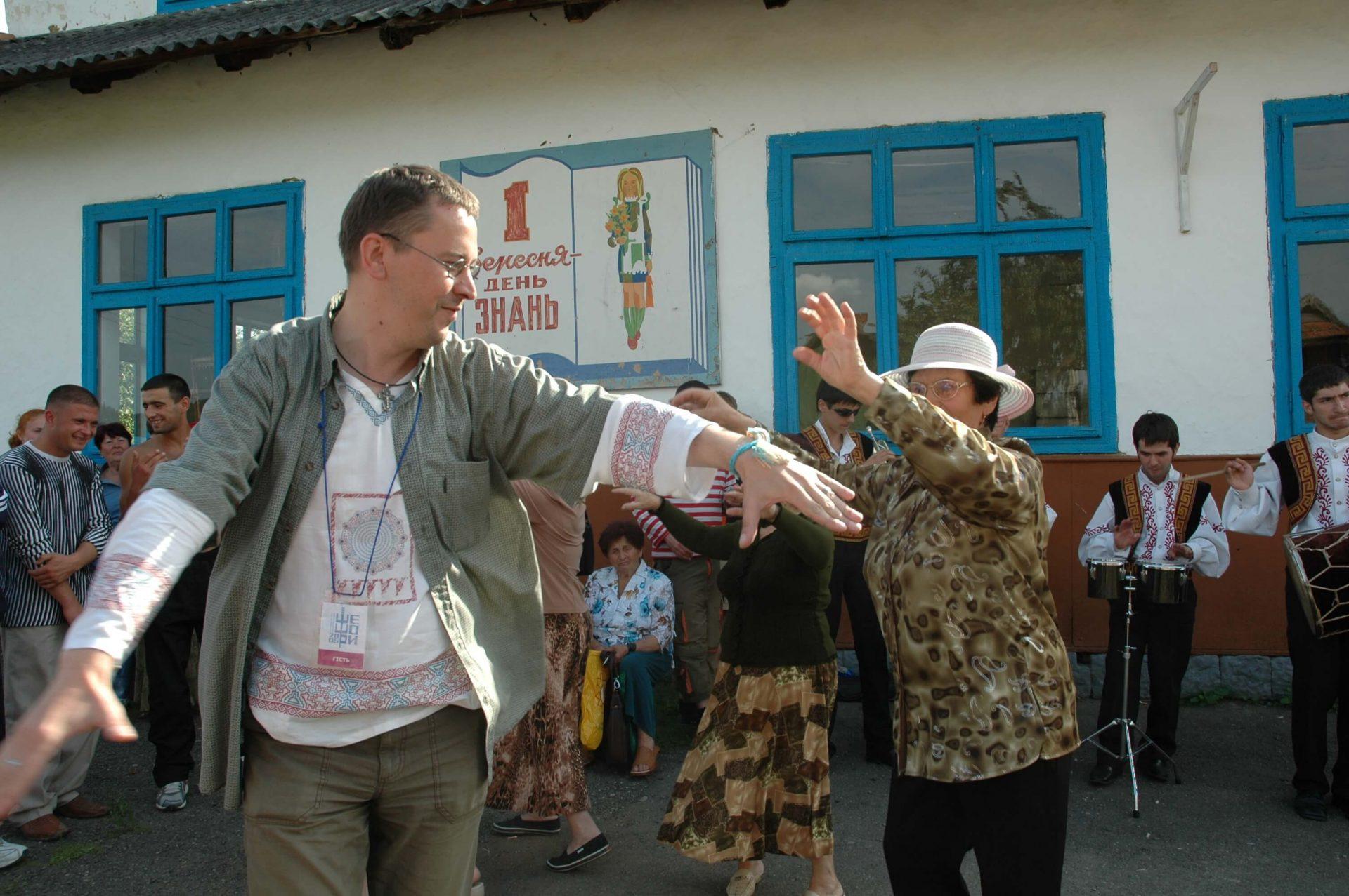 Музиканти в народних костюмах грають під стінами місцевої школи, глядачі розважаються і танцюють на фестивалі в Шешорах