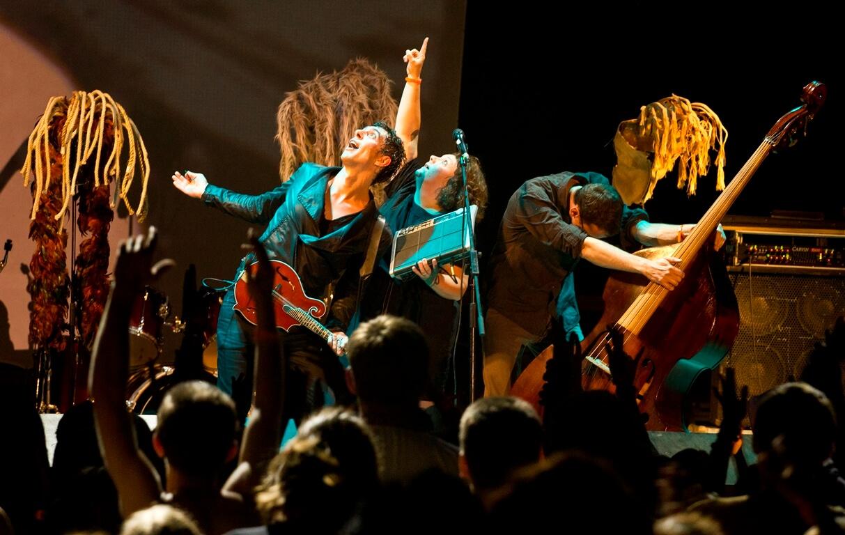 Троє музикантів на сцені, двоє дивляться та показують вгору, а третій, контрабасист, — схилився донизу на нічній сцені фестивалю в Унежі