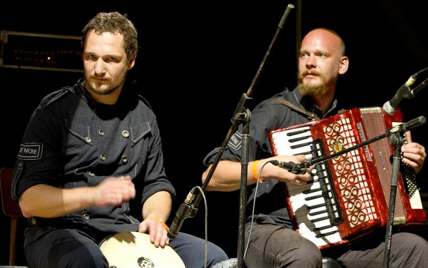 Один музикант грає на перкусійному барабані, інший — на акордеоні на нічній сцені фестивалю в Унежі