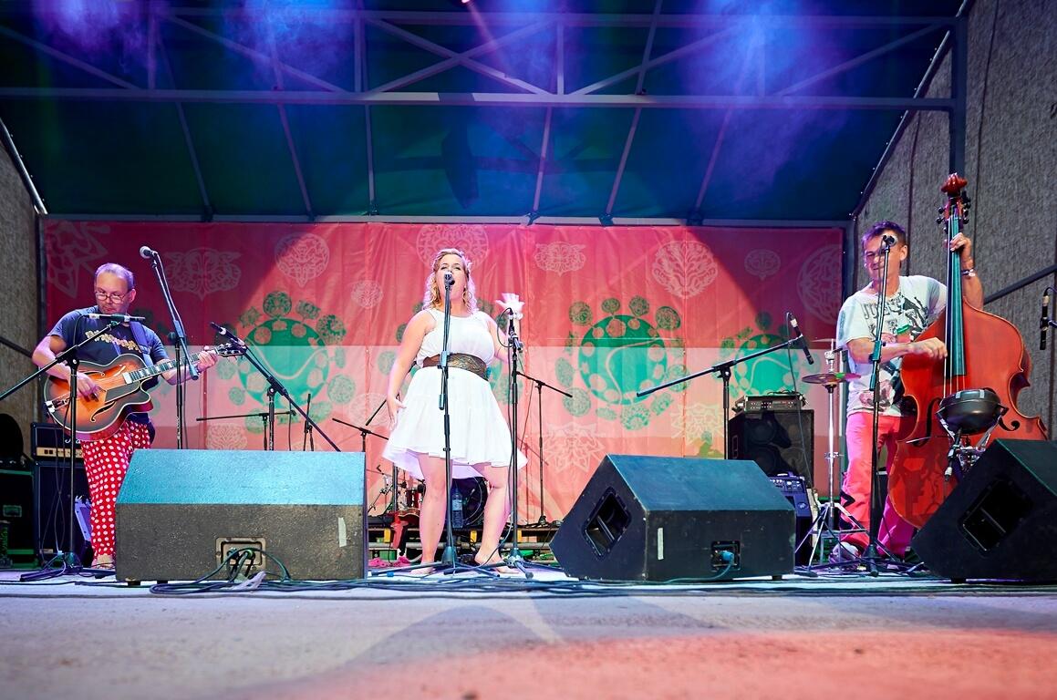 Солістка, одягнута у біле плаття, співає на сцені, зліва від неї контрабасист, справа — гітарист