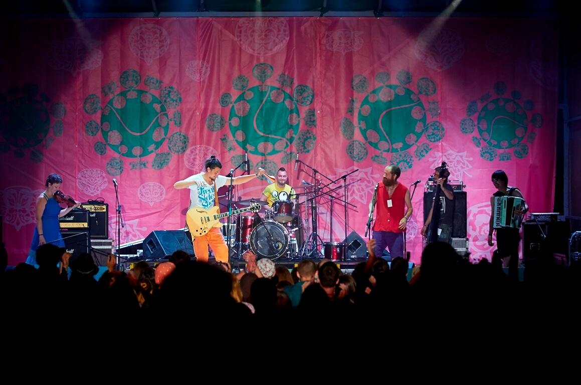 Шестеро музикантів виступають на нічній сцені фестивалю в Унежі, гітарист пританцьовує, розмахуючи руками