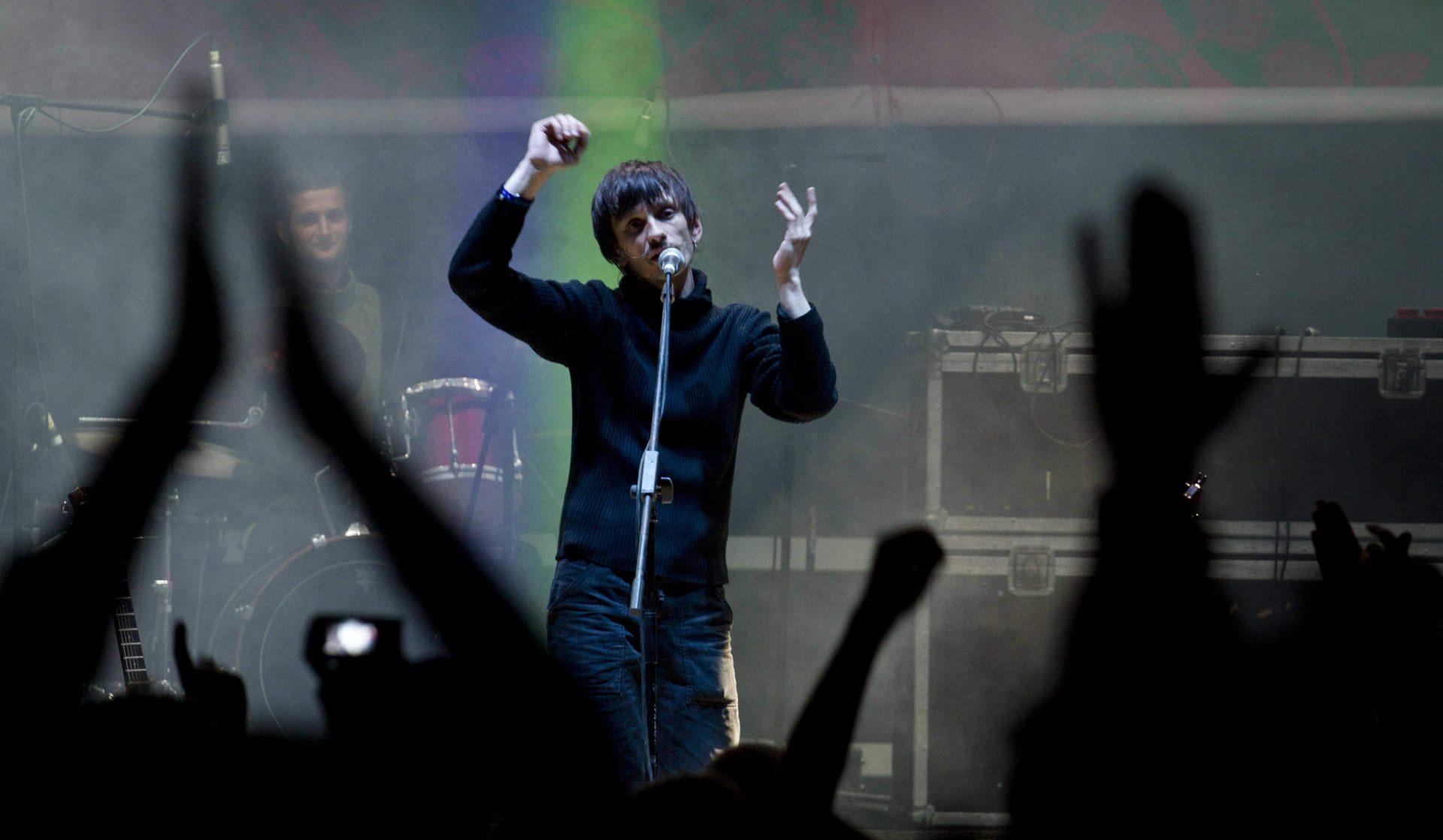 Мар'ян Пиріг співає, піднявши руки догори, на нічній сцені фестивалю в Унежі