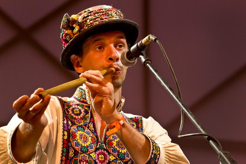 Музикант, в національному буковинському строї з капелюхом, грає на сопілці на сцені фестивалю в Унежі