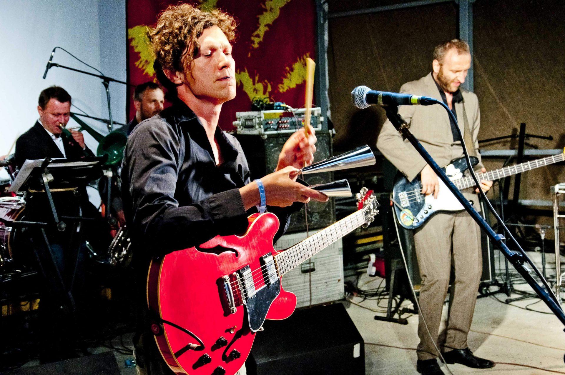 Четверо музикантів виступають на сцені фестивалю в Унежі, в одного із них гітара висить через плече, а у руці він тримає агого, на якому грає, інший музикант у костюмі грає на бас-гітарі