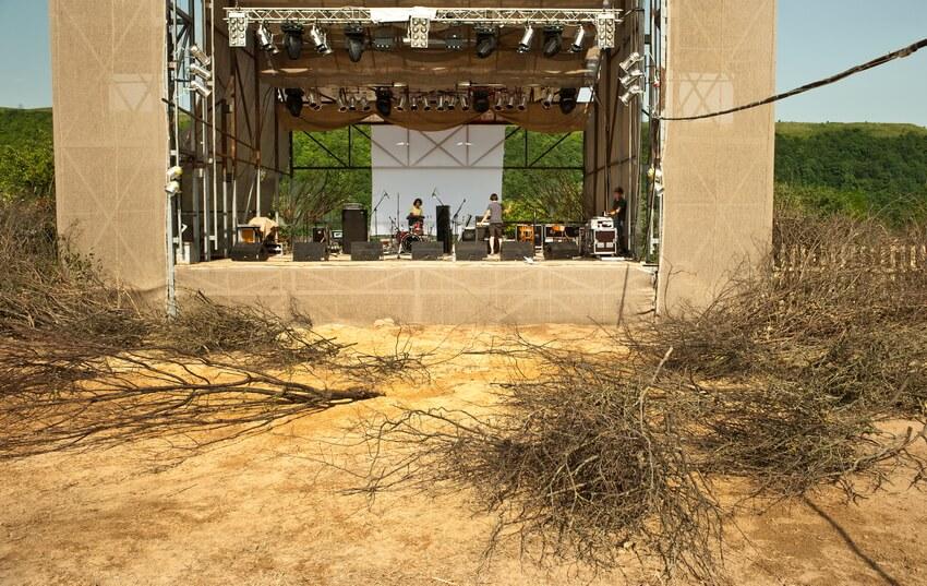 Розкидані сухі гілля дерев перед сценою та музиканти на сцені, які проводять саунд-чек, на фестивалі в Унежі