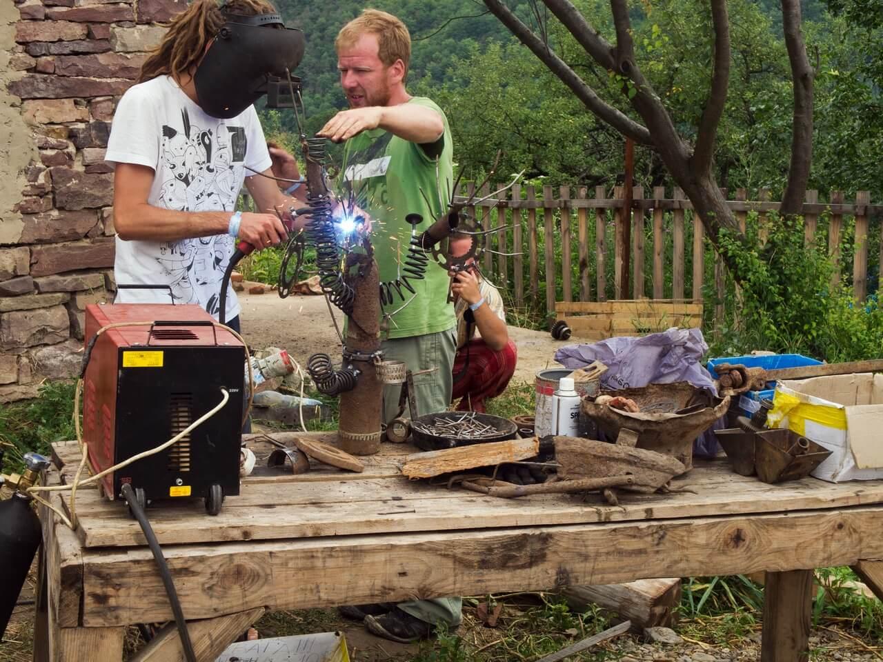 Двоє чоловіків виготовляють металеву скульптуру за допомогою зварювального апарата на фестивалі в Унежі