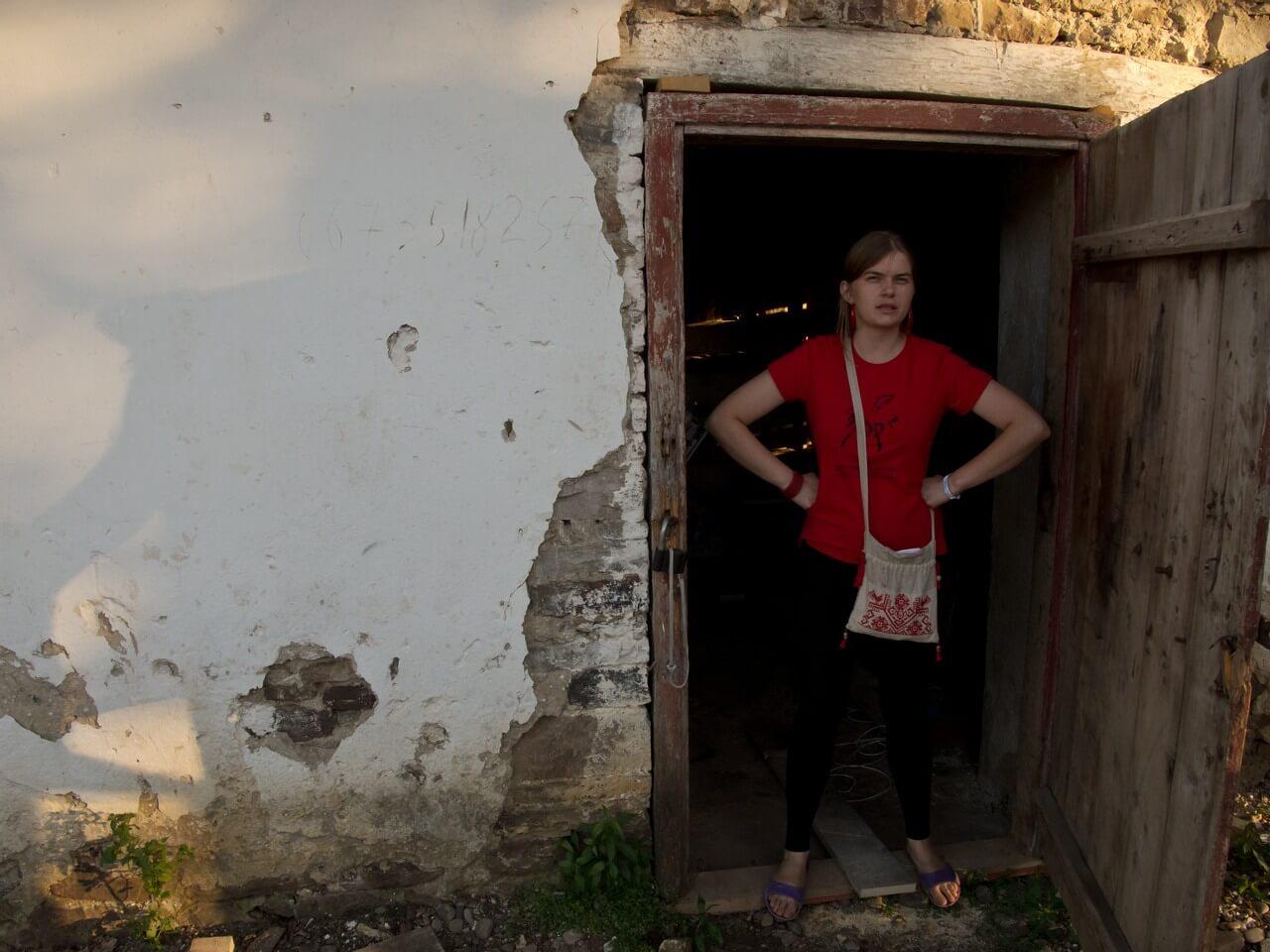 Дівчина стоїть, взявшись руками за боки, у відчинених дверях старої хати на фестивалі в Унежі
