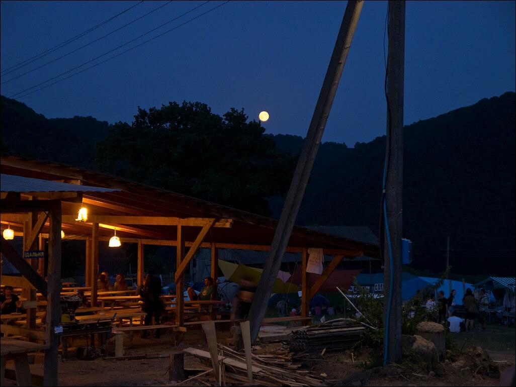 [alt]Дерев'яна альтанка-їдальня вночі на фестивалі в Унежі