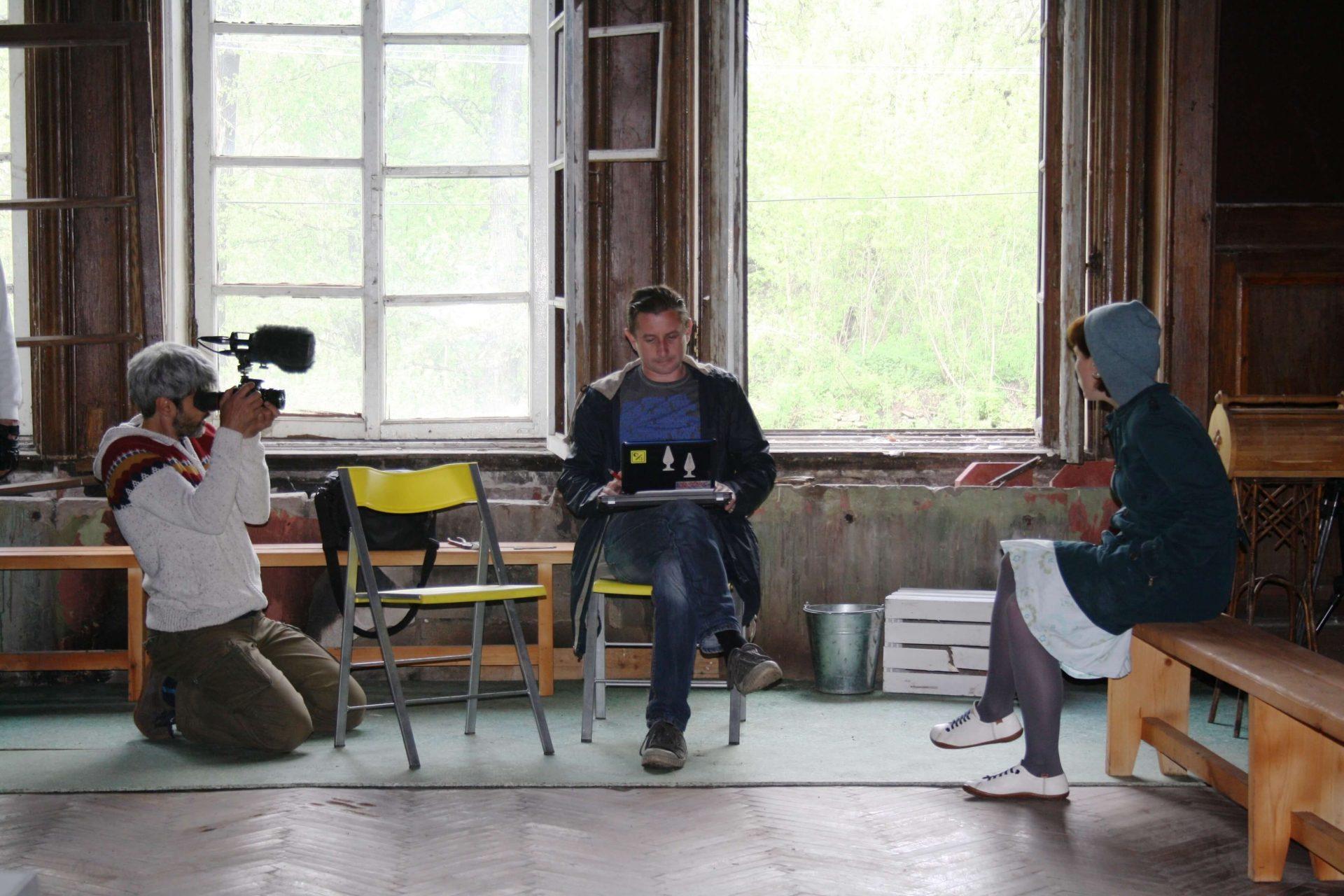 Сергій Жадан сидить на стільці та дивиться у ноутбук, який тримає у себе на колінах, зліва від нього — відео оператор, справа — Оля Михайлюк