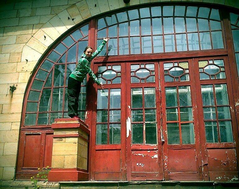 Жінка стоїть на колоні біля вхідних дверей садиби Мсциховського та показує руками на них