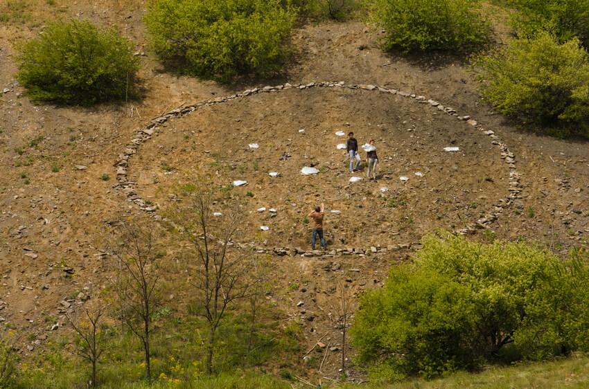 Троє людей на схилі гори виклали велике коло із каміння на фестивалі ARTPOLE.LU
