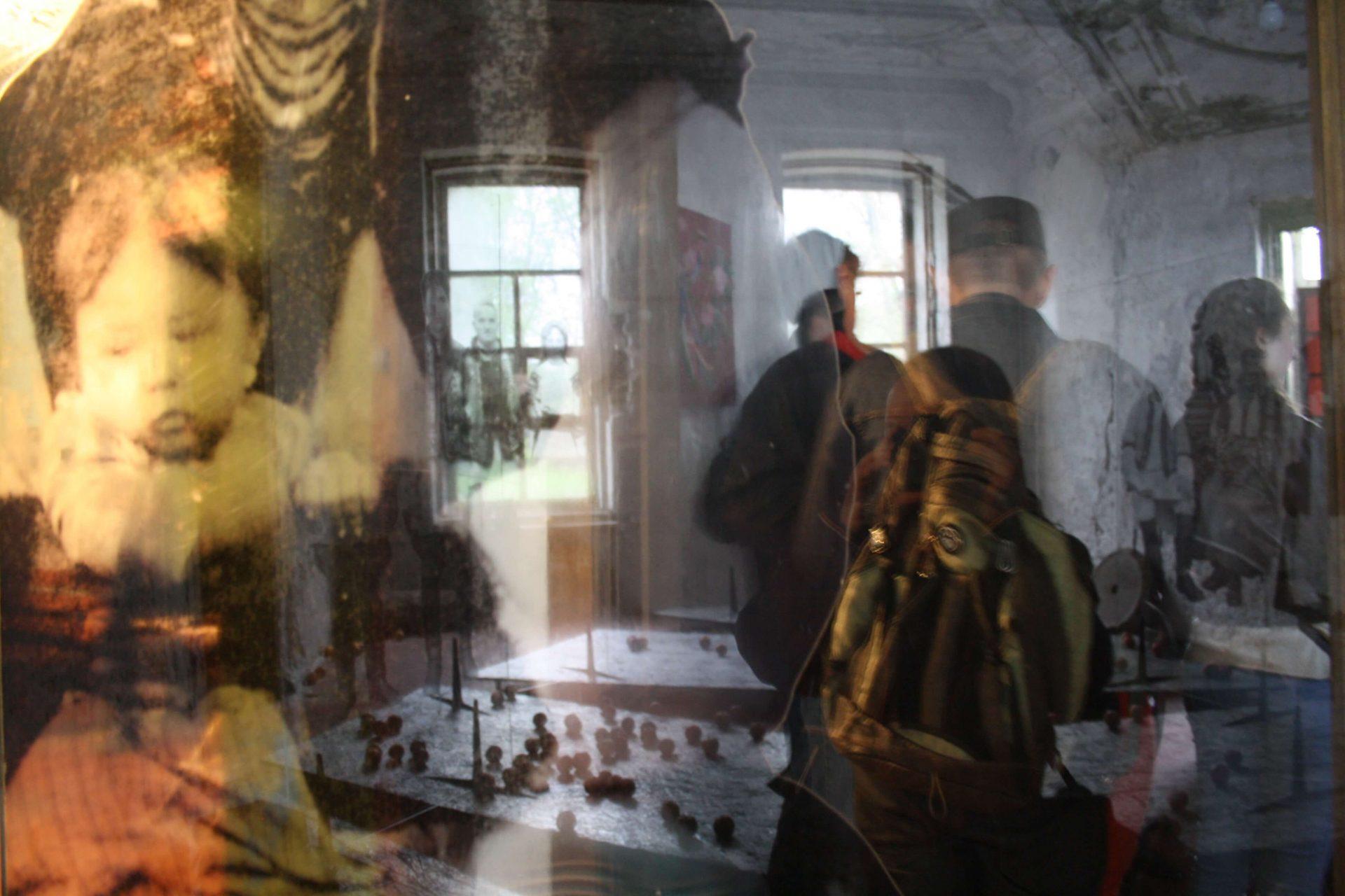 Фото людей, зображення яких відбивається у склі
